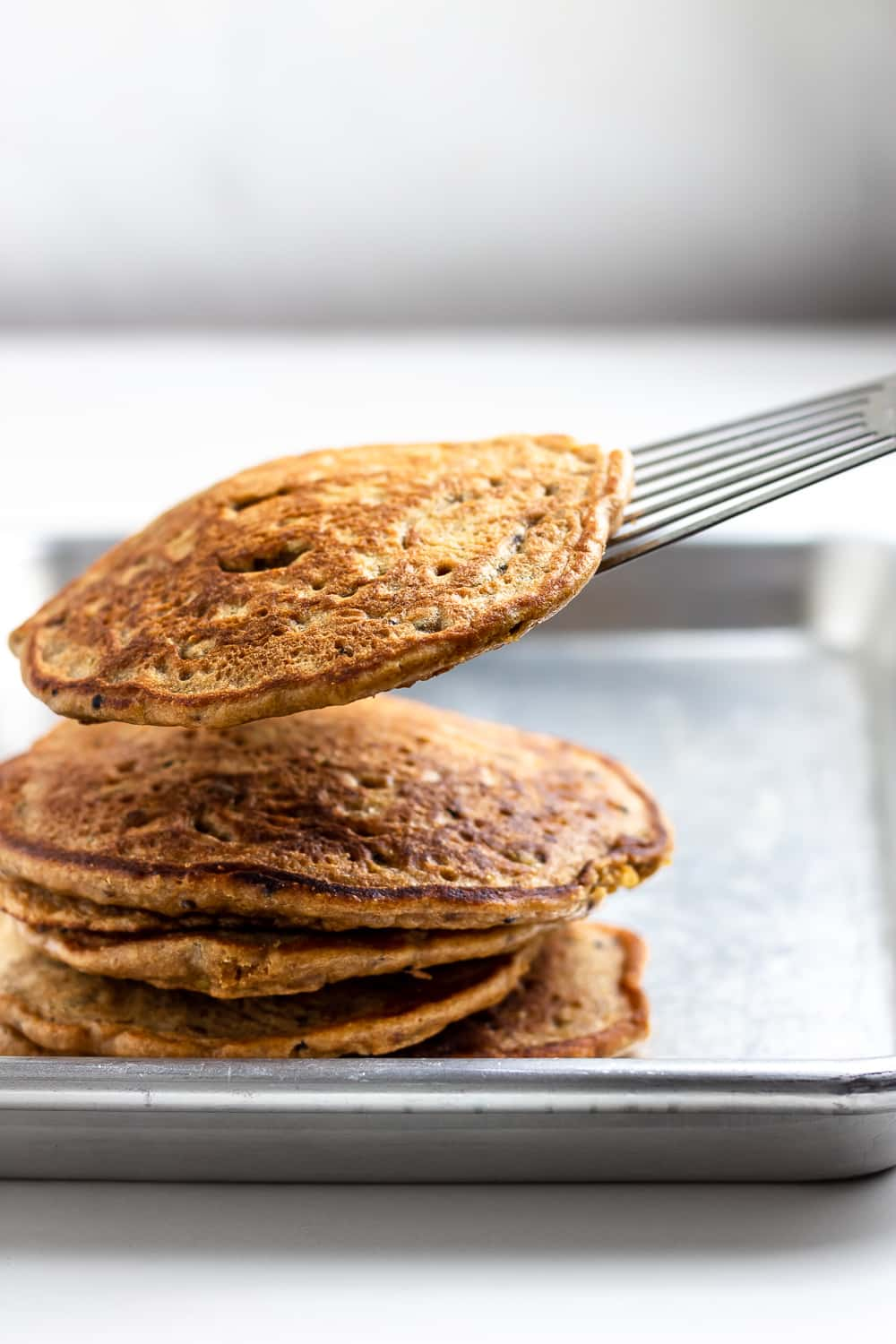 A stack of whole grain pancakes on a rimmed baking sheet with thin spatula
