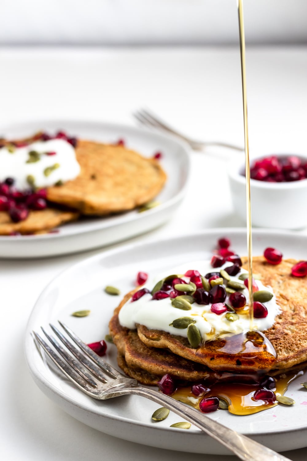 healthy whole grain pancakes on white plates with pomegranates, pumpkin seeds, whole milk yogurt, and a drizzle of maple syrup