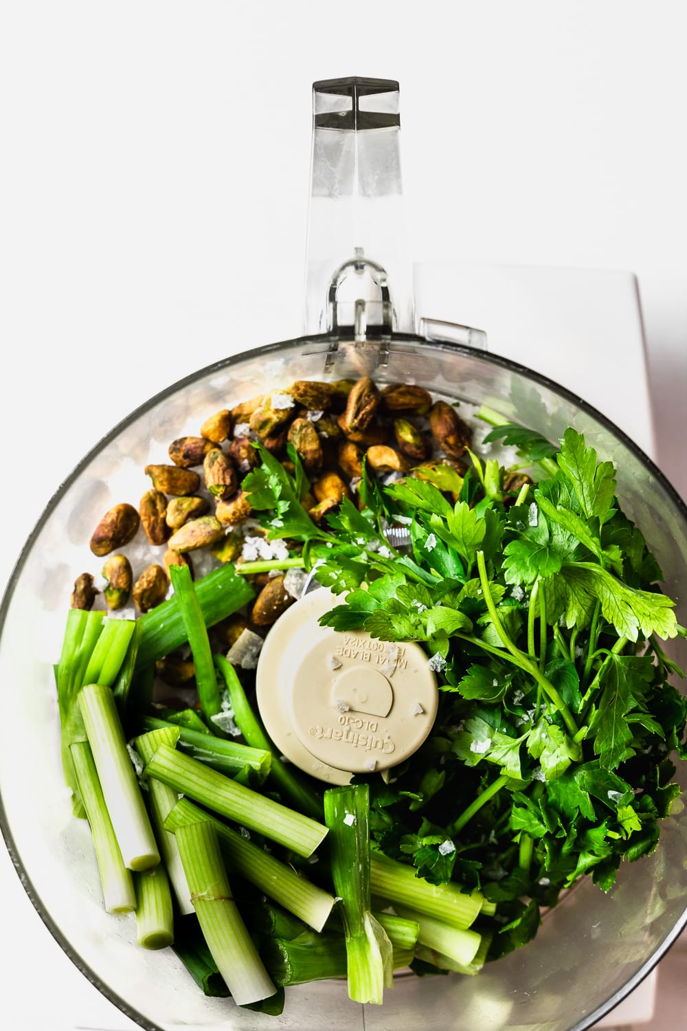 food processor bowl with pistachios, parsley, scallions, and flaky sea salt
