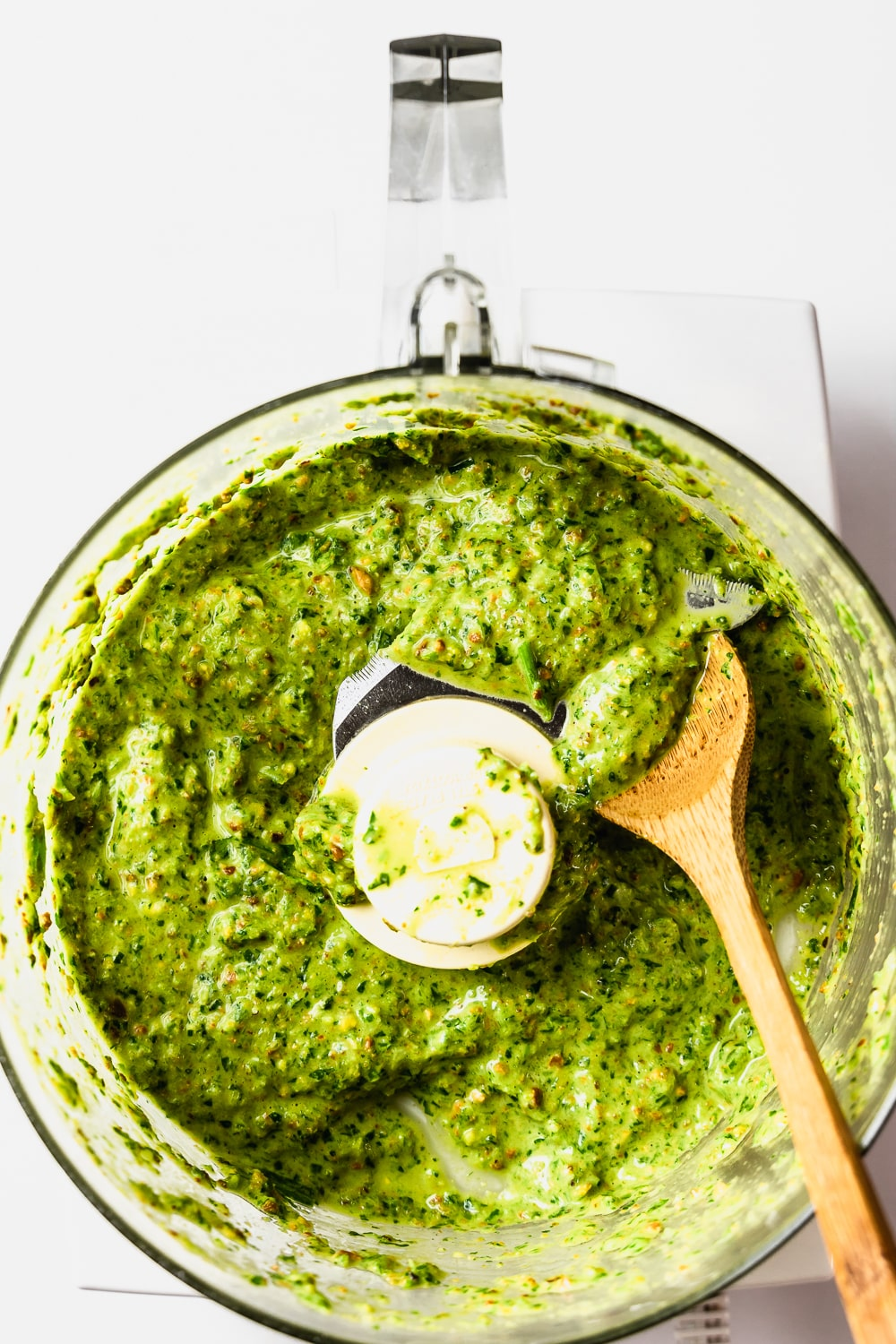 food processor bowl with pistachio pesto and wooden spoon
