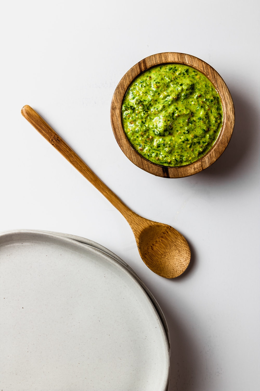 small wooden bowl with quick pistachio pesto, wooden spoon, and stack of grey plates