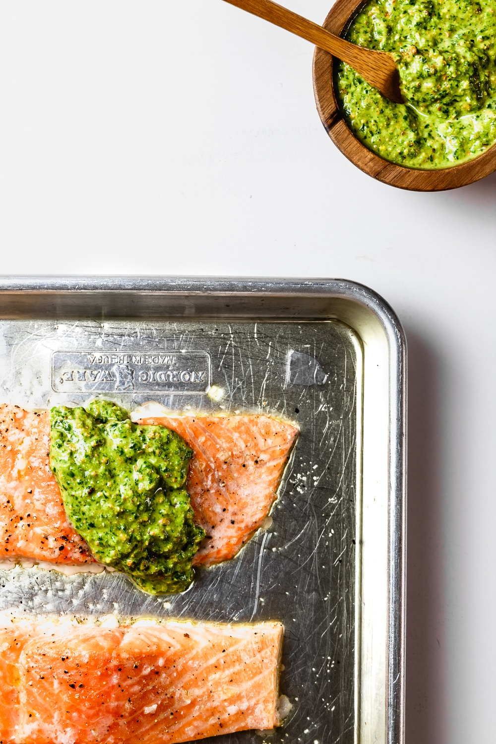 fillet of slow roasted salmon with pistachio pesto on rimmed baking sheet and small wooden bowl of pistachio pesto on the side with wooden spoon