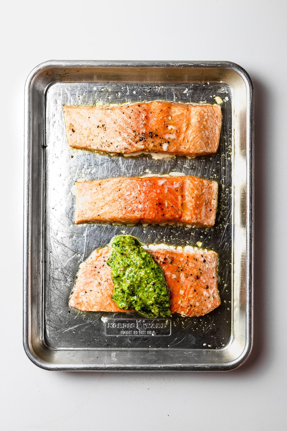 three slow roasted salmon fillets with quick pistachio pesto on a rimmed baking sheet
