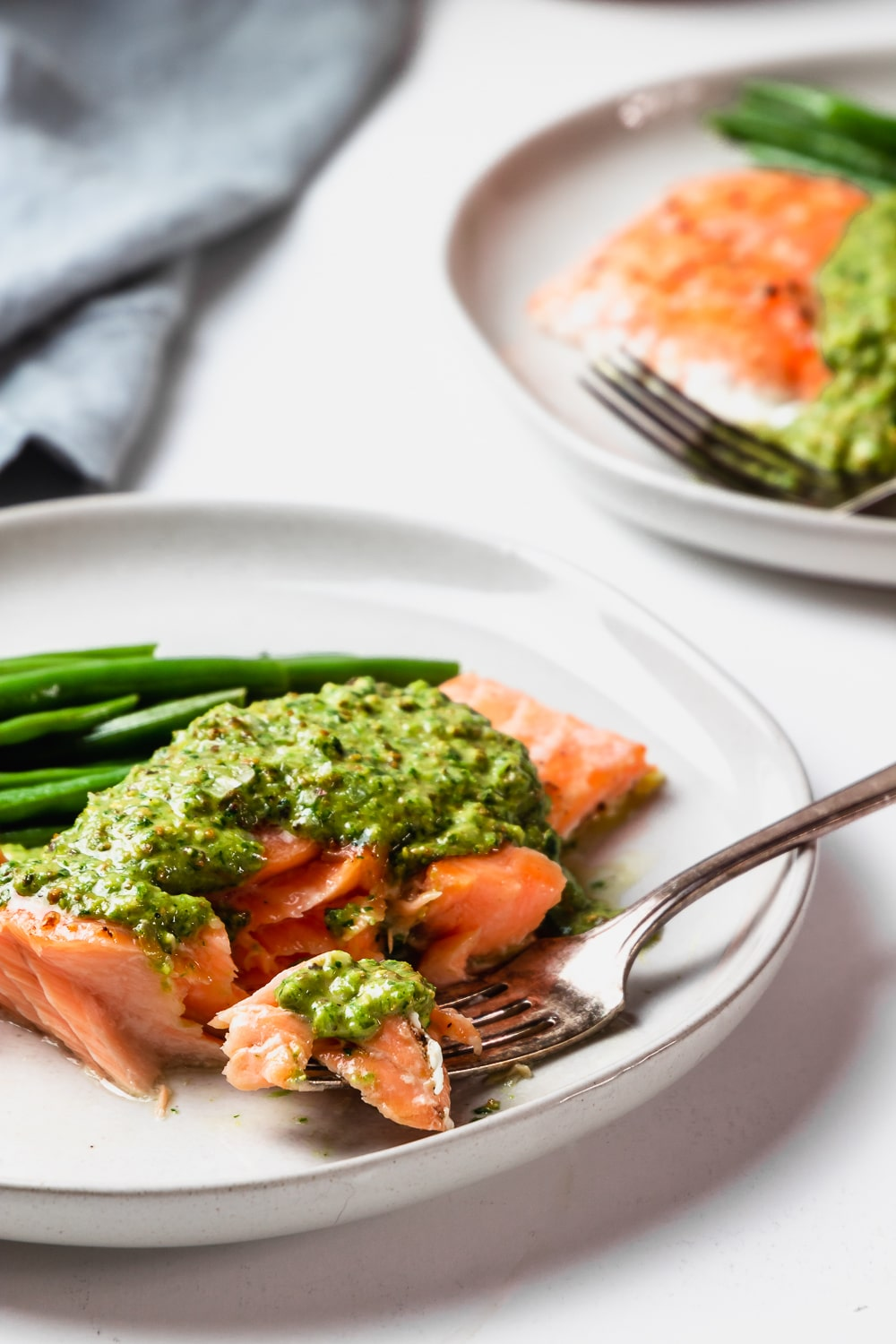 two plates with slow roasted salmon fillets with pistachio pesto and green beans