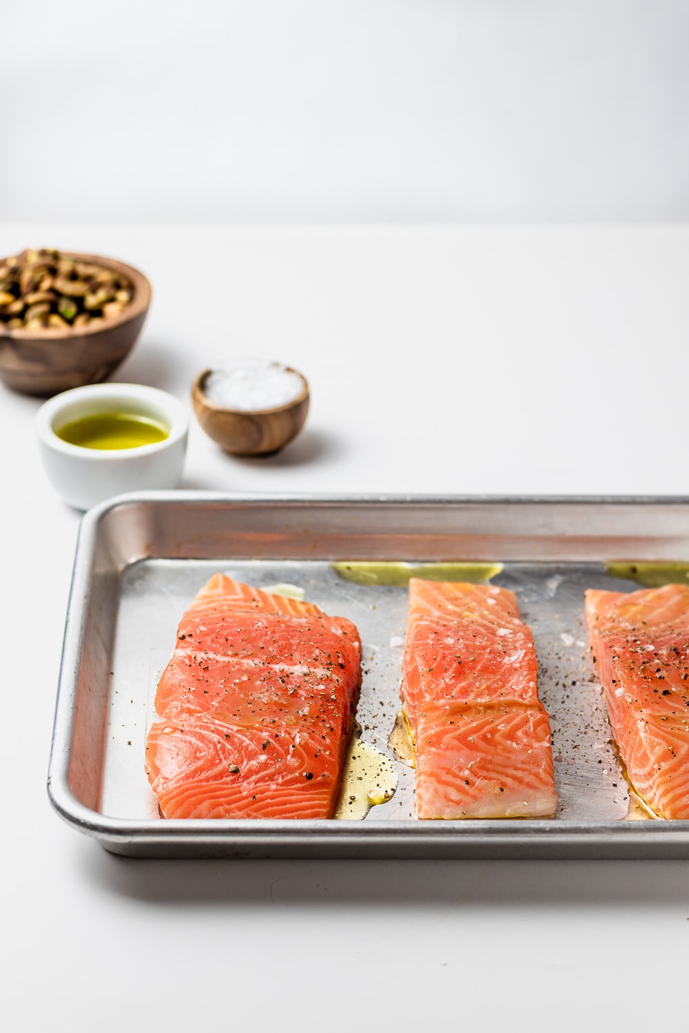 rimmed baking sheet with salmon fillets, bowls of pistachios, olive oil and salt in the background