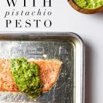 "fillet of slow roasted salmon with pistachio pesto on rimmed baking sheet and small wooden bowl of pistachio pesto on the side with wooden spoon and text overlay that reads ""slow roasted salmon with pistachio pesto"""