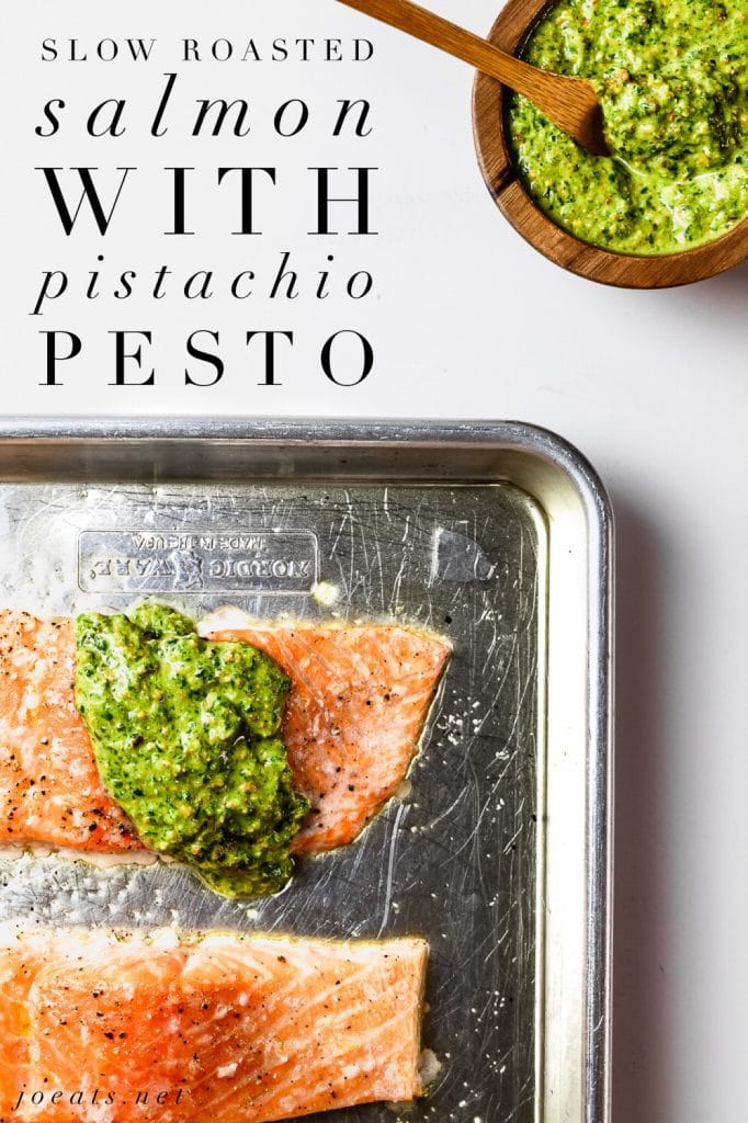 """fillet of slow roasted salmon with pistachio pesto on rimmed baking sheet and small wooden bowl of pistachio pesto on the side with wooden spoon and text overlay that reads """"slow roasted salmon with pistachio pesto"""""""
