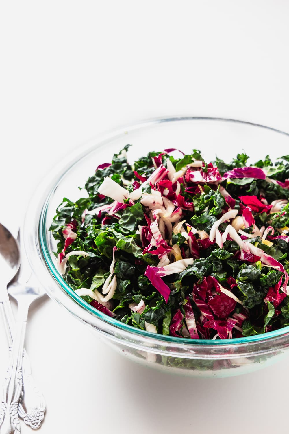 large glass bowl with shredded kale, radicchio and endive, mixed up. Serving utensils on the side
