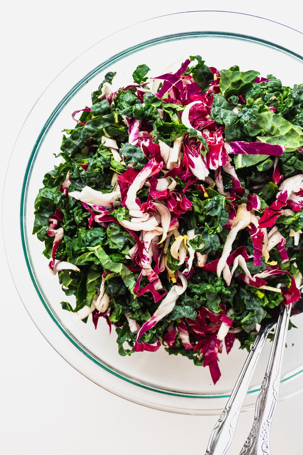 large glass bowl with shredded kale, radicchio and endive, mixed up