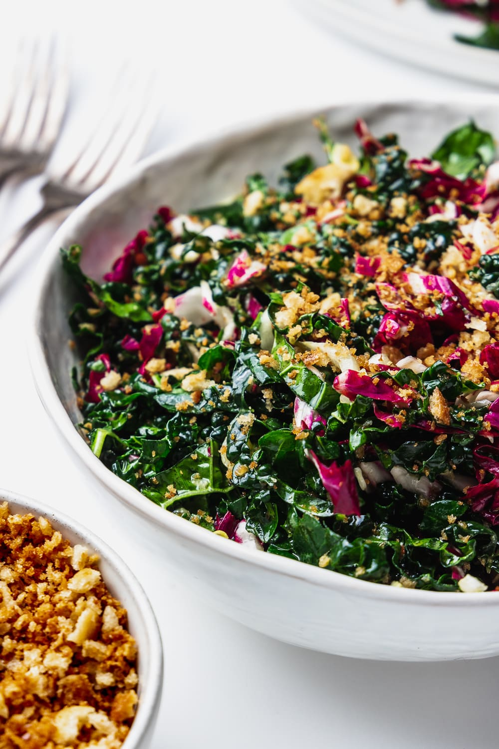 close up of kale winter slaw with buttered breadcrumbs and two forks