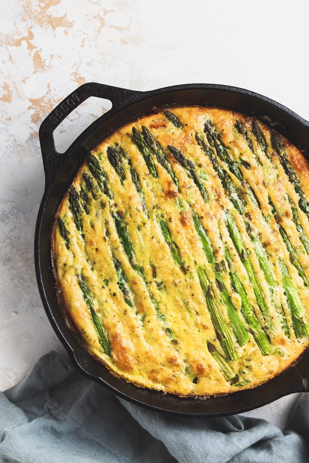 cooked asparagus and ham frittata in a cast iron skillet with blue napkin