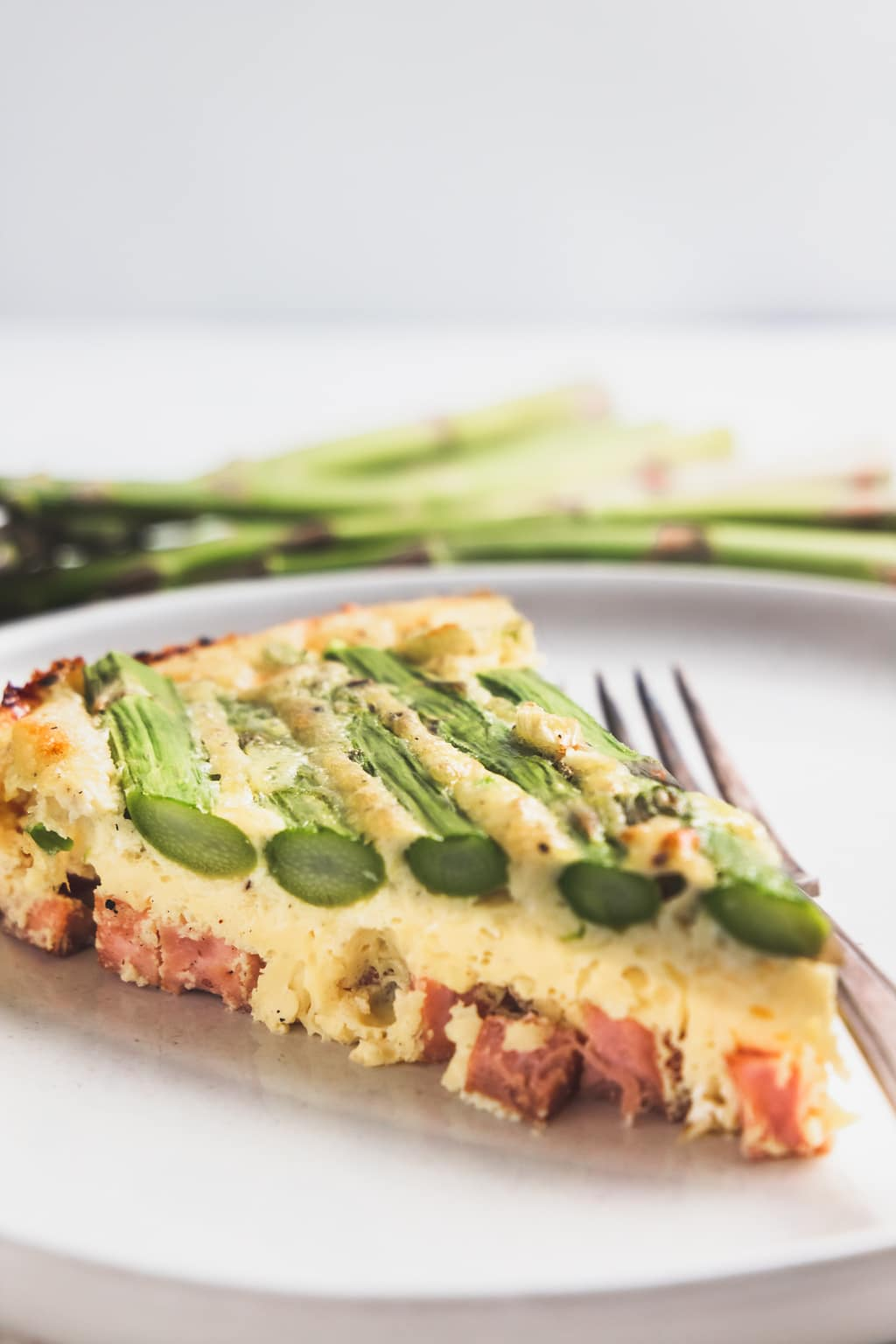 slice of asparagus and ham frittata on a white plate with silver fork