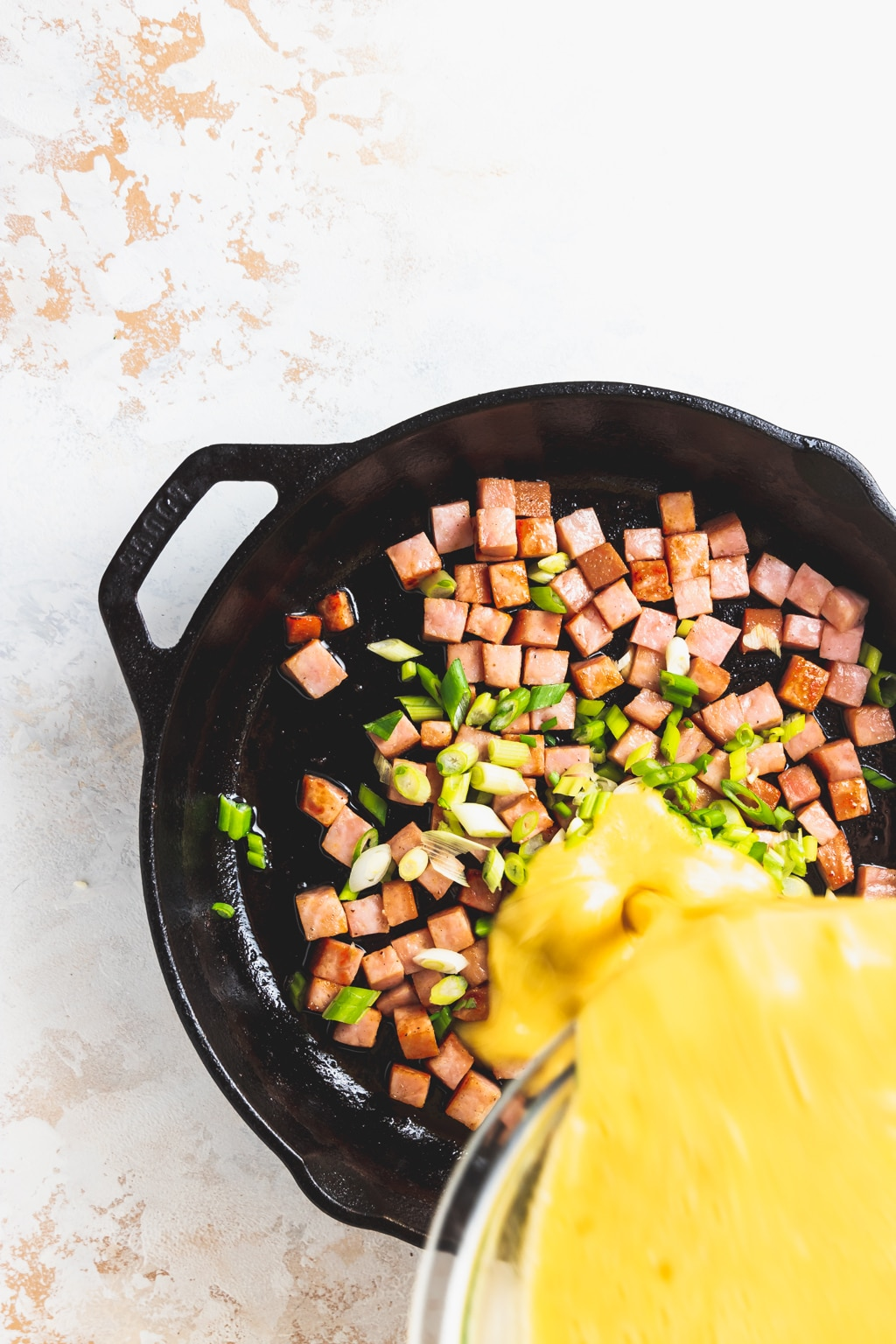 cubed ham and sliced scallions with beaten eggs being poured into cast iron skillet