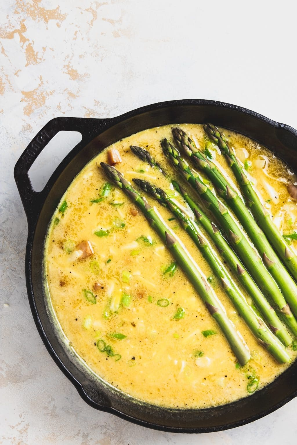 cast iron pan with raw eggs and asparagus spears
