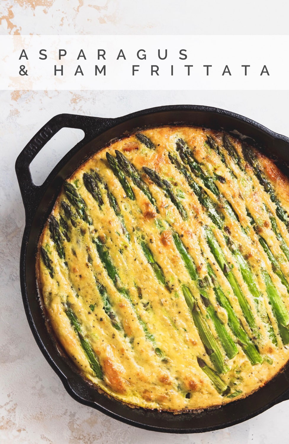 "cooked asparagus and ham frittata in cast iron skillet with the text overlay that reads ""asparagus & ham frittata"""