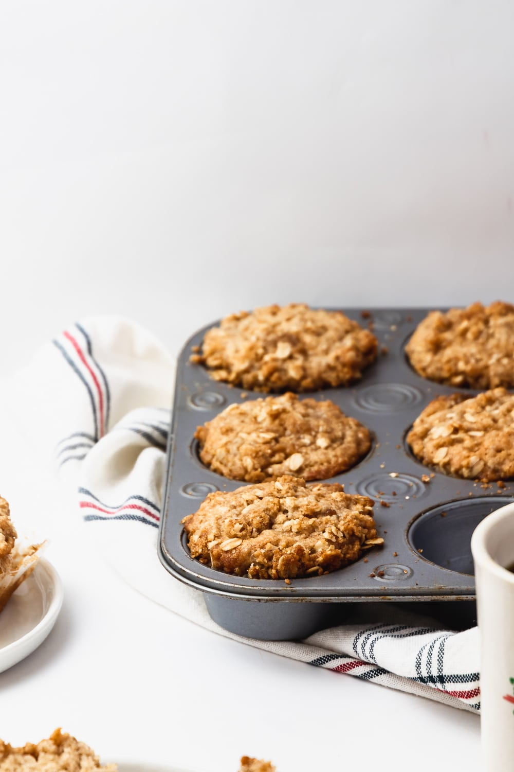 metal muffin tin with five brown sugar oatmeal muffins on top of striped kitchen towel. One muffin missing.
