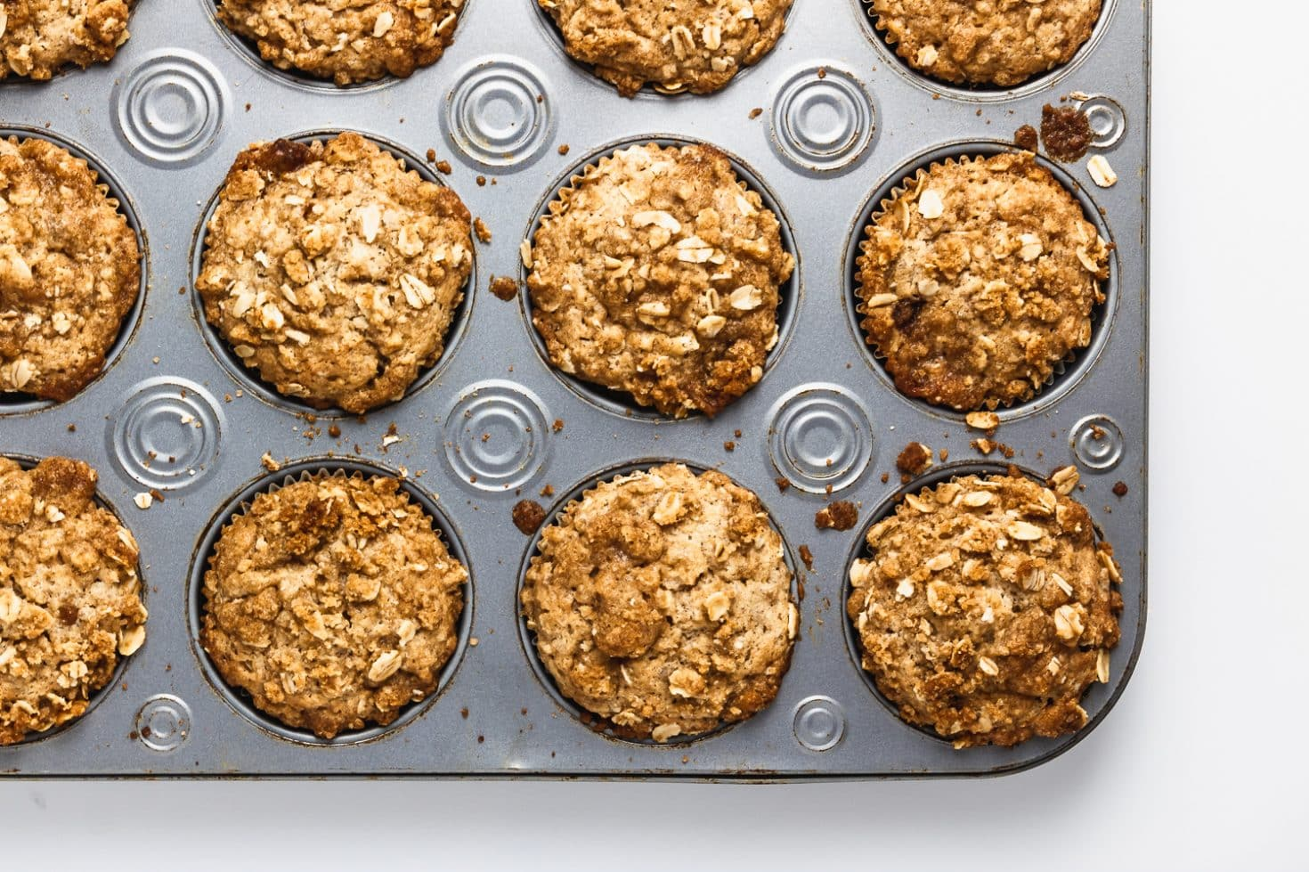 overhead shot of baked brown sugar oatmeal muffins in metal muffin tin