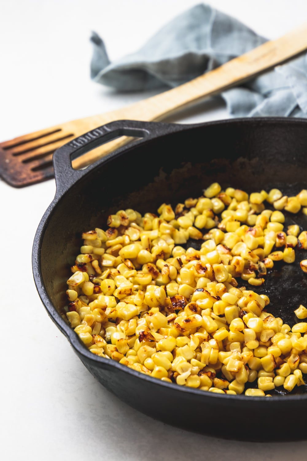 cast iron pan with charred corn, wooden spatula, and blue napkin