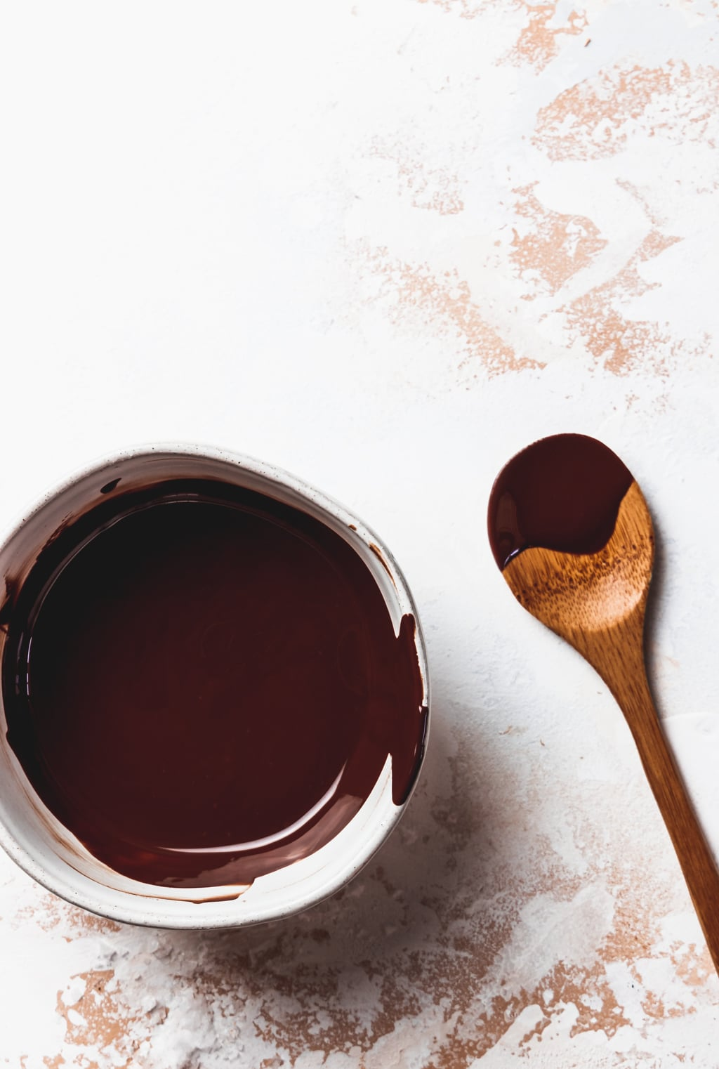 melted chocolate in a small white bowl with wooden spoon