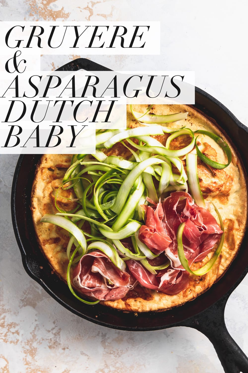"cast iron skillet with gruyere dutch baby pancake, raw asparagus, and sliced prosciutto. Text overlay that reads ""gruyere & asparagus dutch baby"""