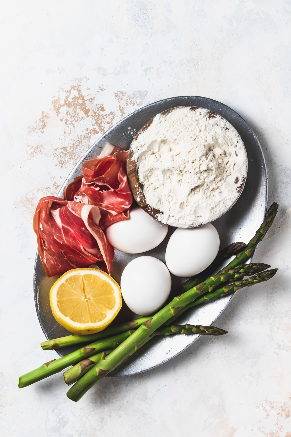 silver plate with flour, eggs, lemon, asparagus, and prosciutto