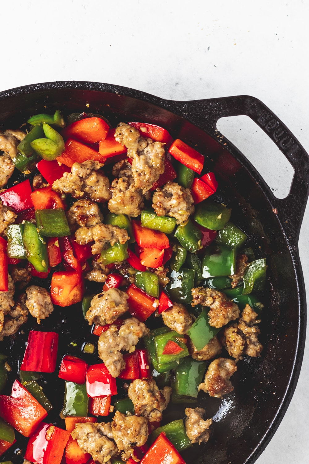 cast iron skillet with browned sausage and red and green peppers
