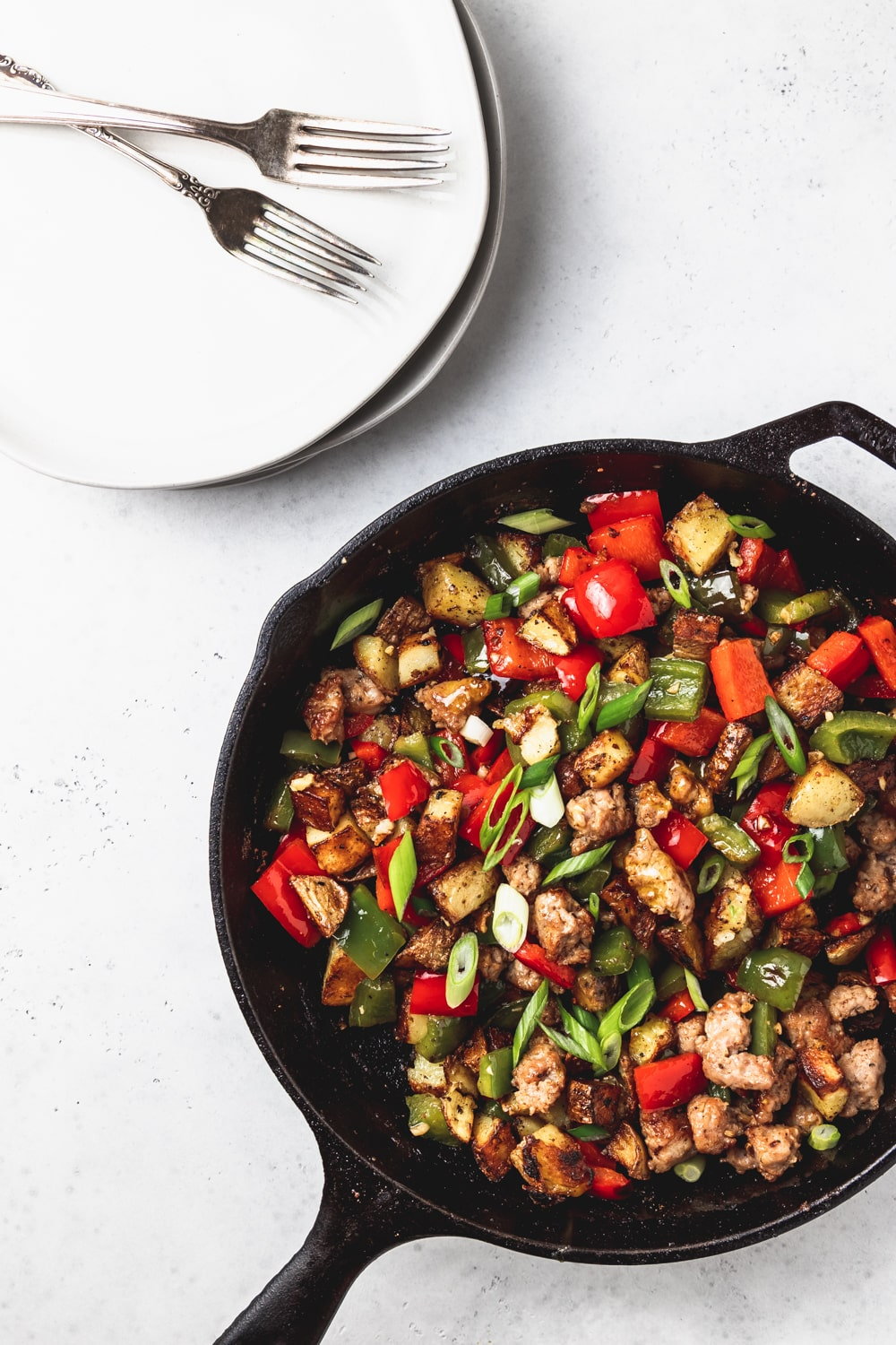 cast iron skillet with sausage and peppers breakfast hash, two plates, two forks