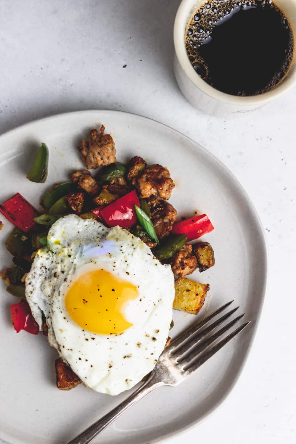 sunny side up egg on top of a plate of breakfast hash with a fork and cup of black coffee