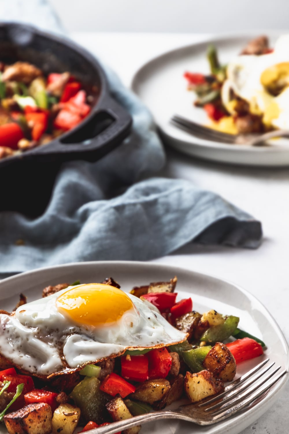 sunny side up egg on top of a plate of sausage and peppers breakfast hash