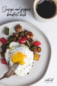 "grey plate with breakfast hash and fried egg and cup of coffee with text overlay that reads ""sausage and peppers breakfast hash"" and ""joeats.net"""