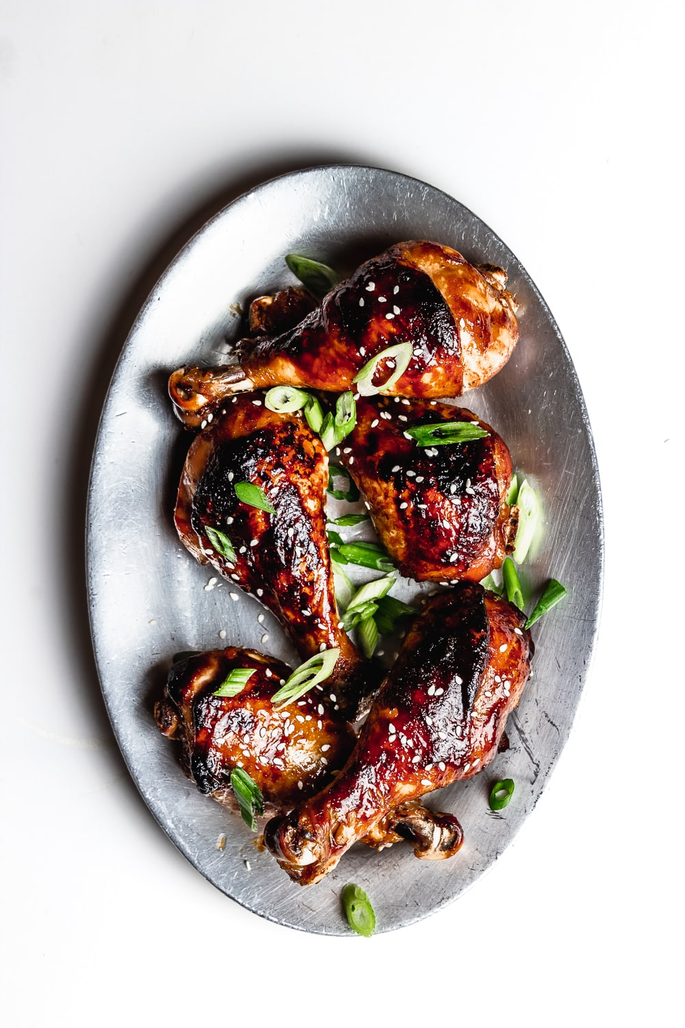 Sesame soy chicken drumsticks with sesame seeds and sliced scallions on a silver plate