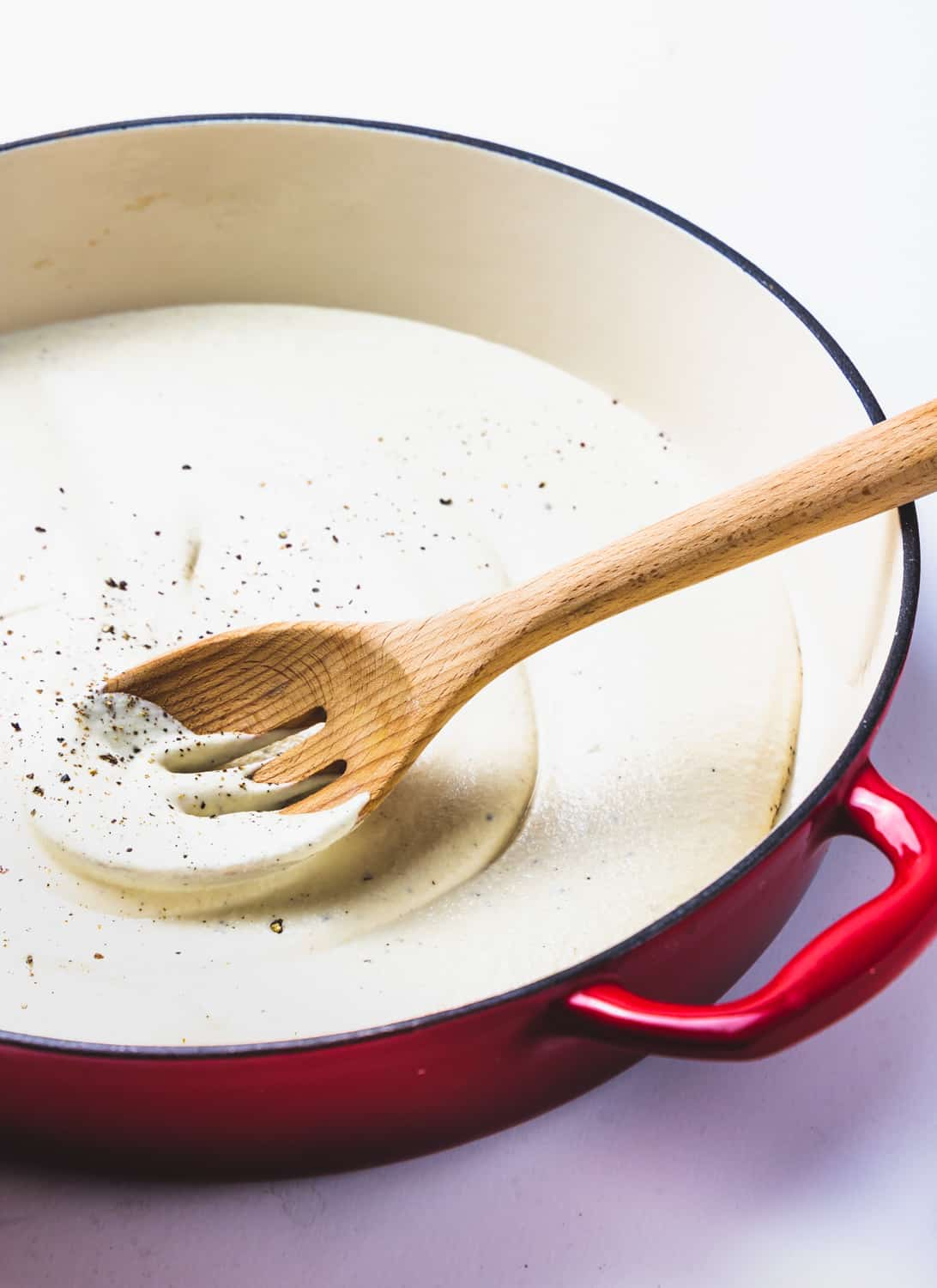 creamy roasted garlic cashew sauce in red pan with wooden spoon