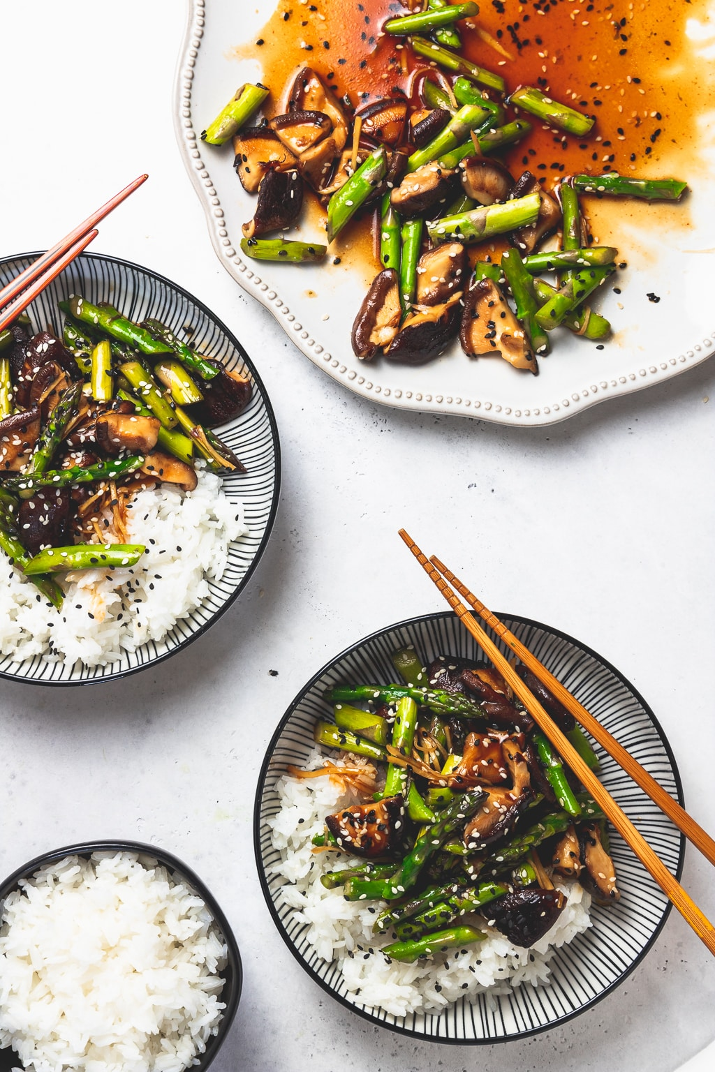 asparagus and mushroom stir fry in bowls and on a plate with white rice and chopsticks