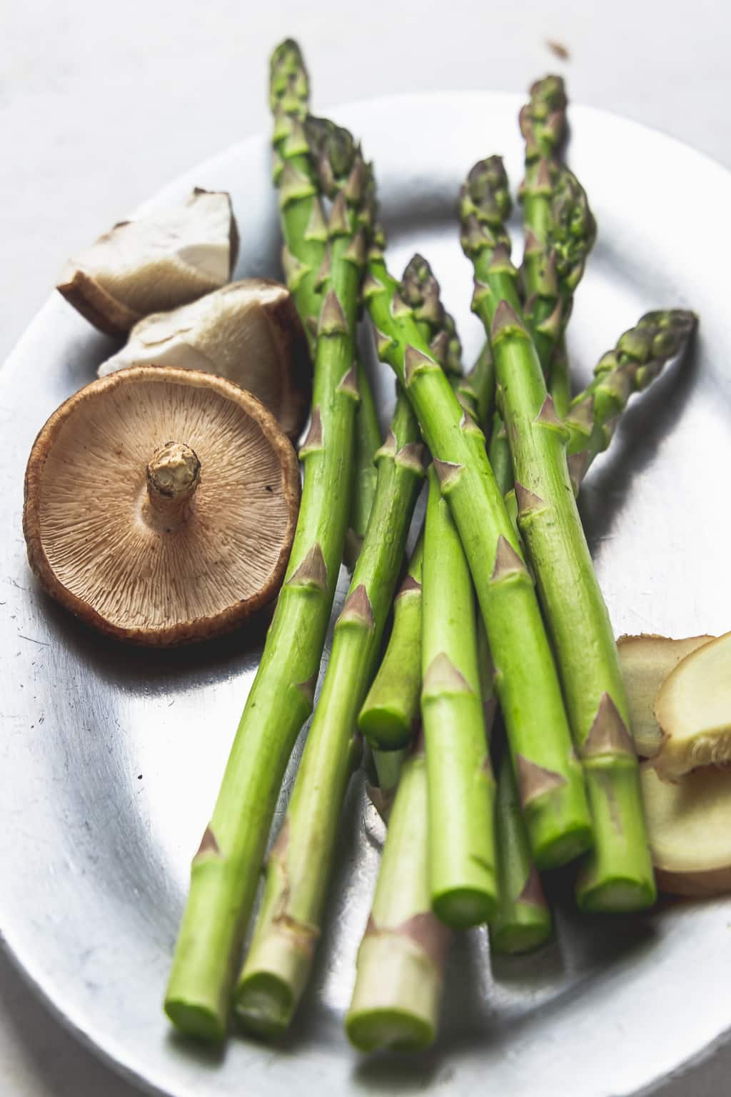 silver plate with asparagus spears and shiitake mushrooms