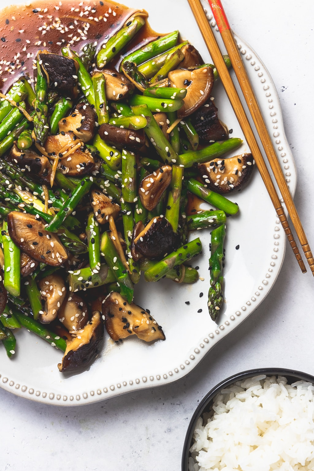 platter of asparagus mushroom stir fry with chopsticks and white rice