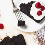 overhead of slice of chocolate loaf cake with whipped cream and raspberries