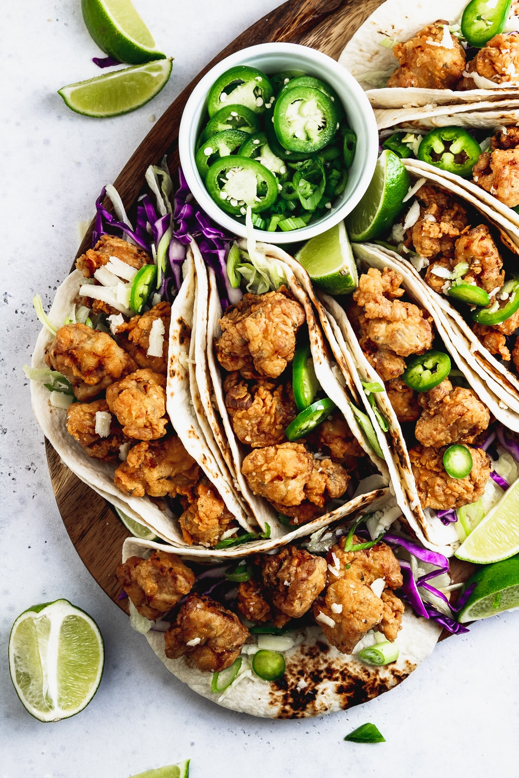 overhead of fried chicken tacos on a wooden board with limes