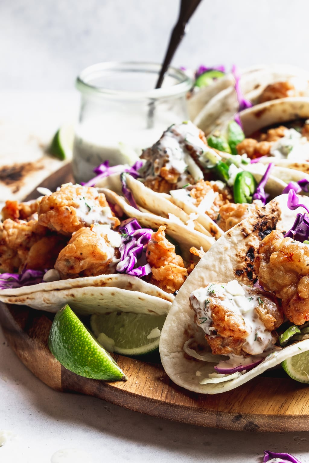 close up of fried chicken tacos with garlic ranch on a wooden board with limes