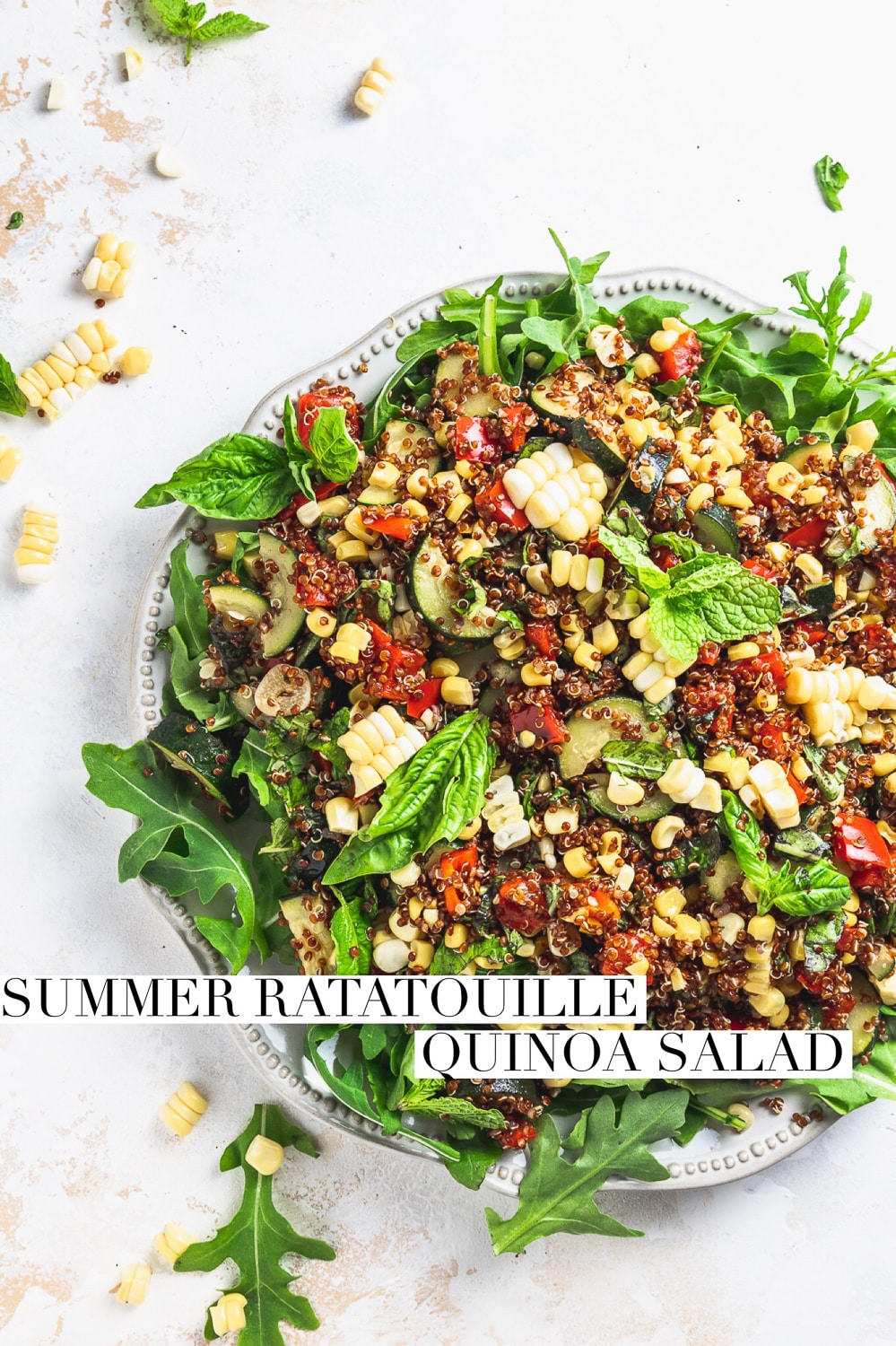 "zucchini corn quinoa salad on a plate with arugula and herbs with text overlay that reads ""summer ratatouille quinoa salad"""