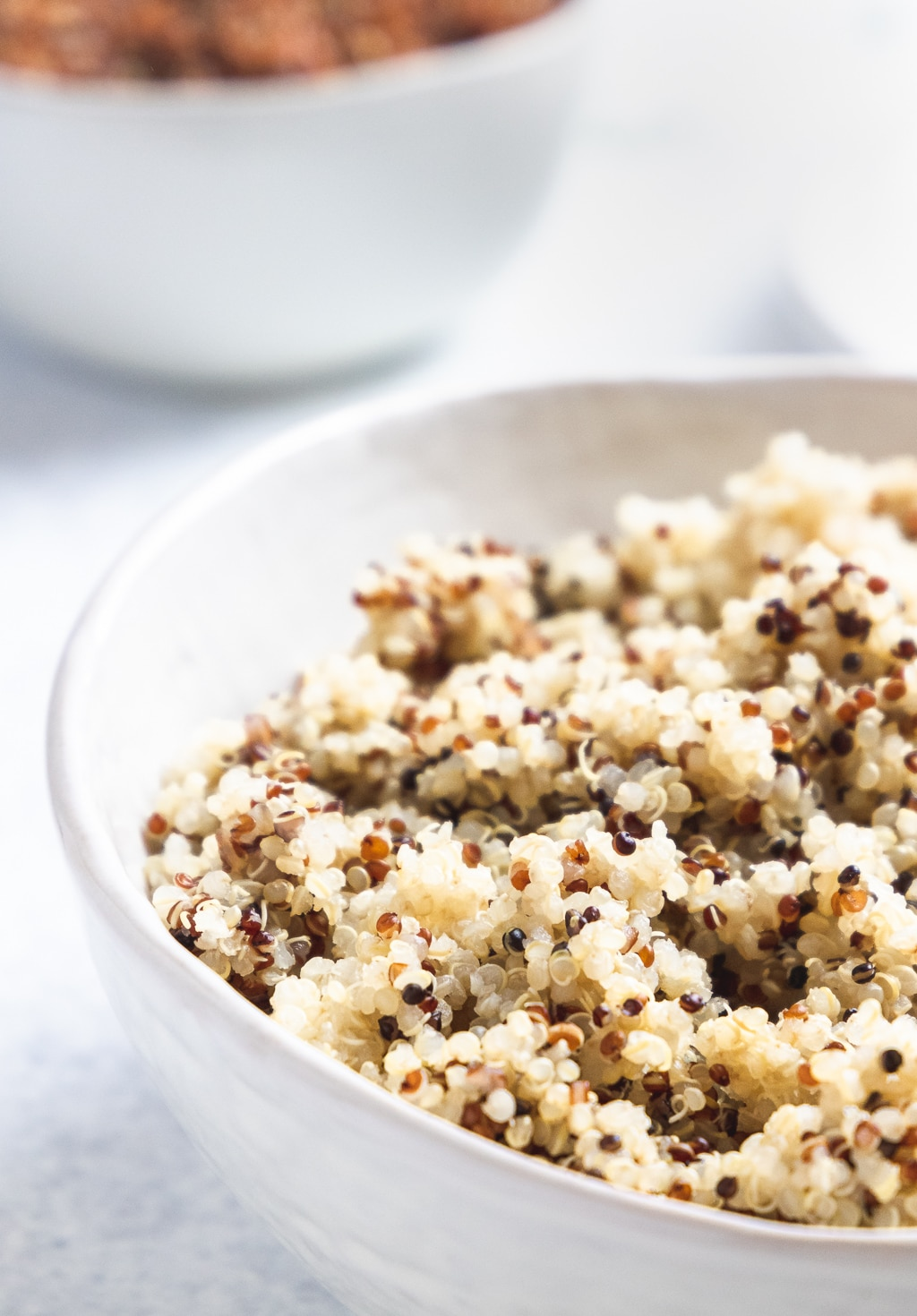 close up of cooked tricolor quinoa in a white serving bowl