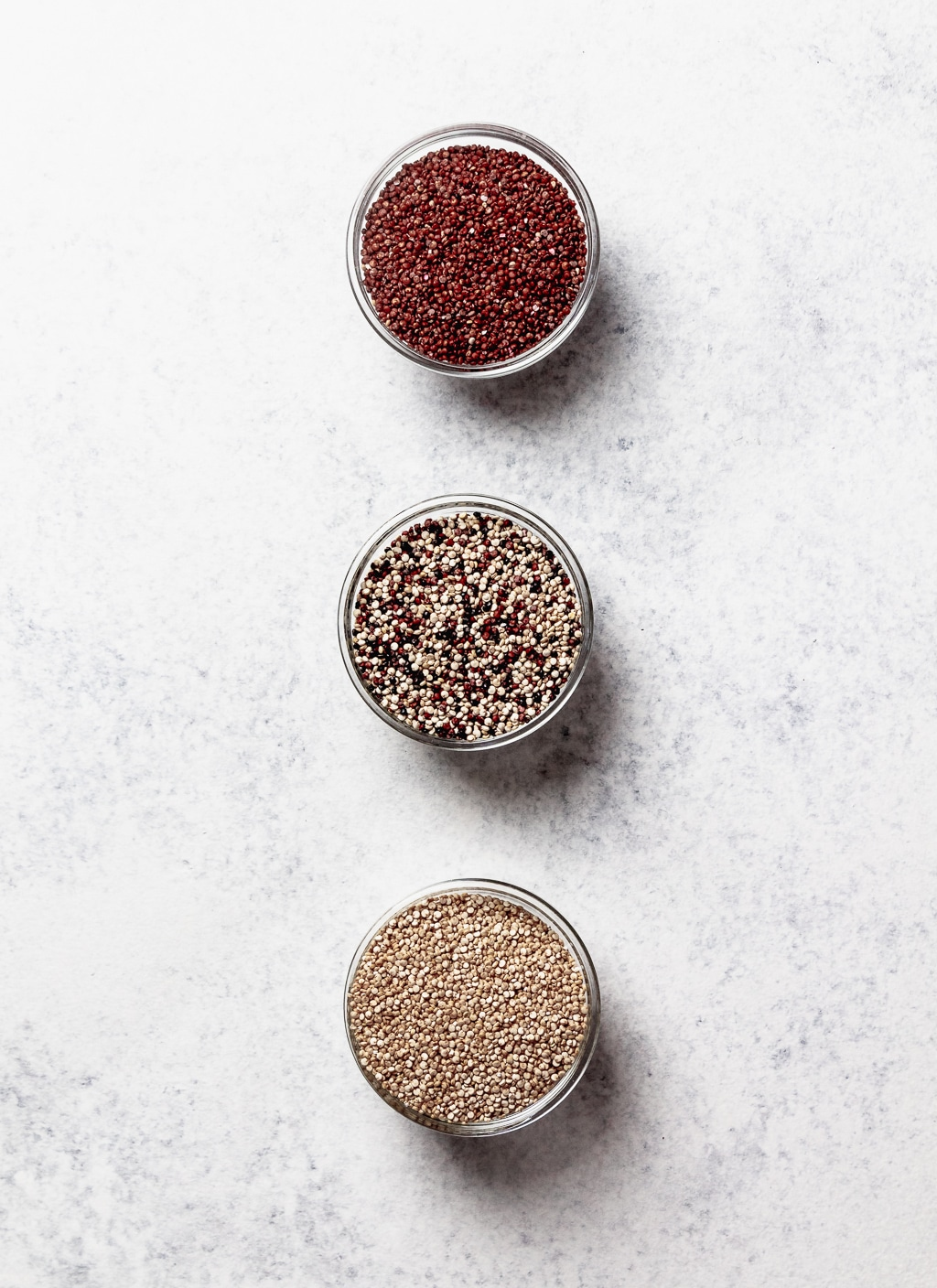 red white and tricolor quinoa, uncooked in bowls lined up vertically