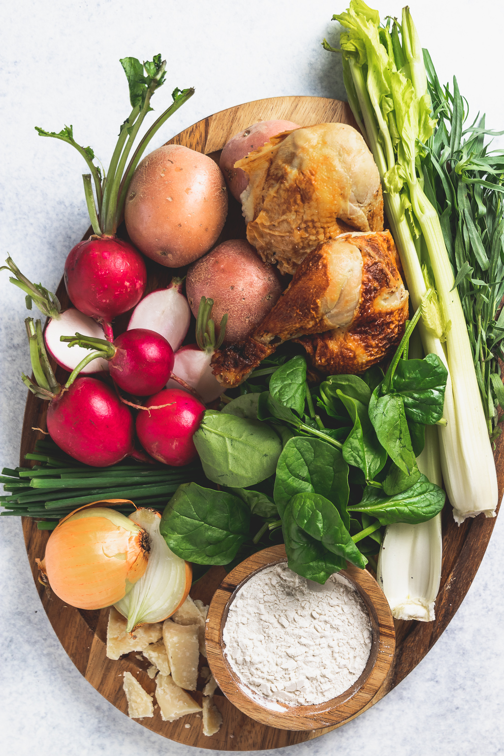 wooden platter with spring vegetables and other ingredients for the recipe