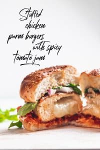 """stuffed chicken parm burger cut in half with cheese in the middle and text overlay that reads """"stuffed chicken parm burgers with spicy tomato jam"""""""