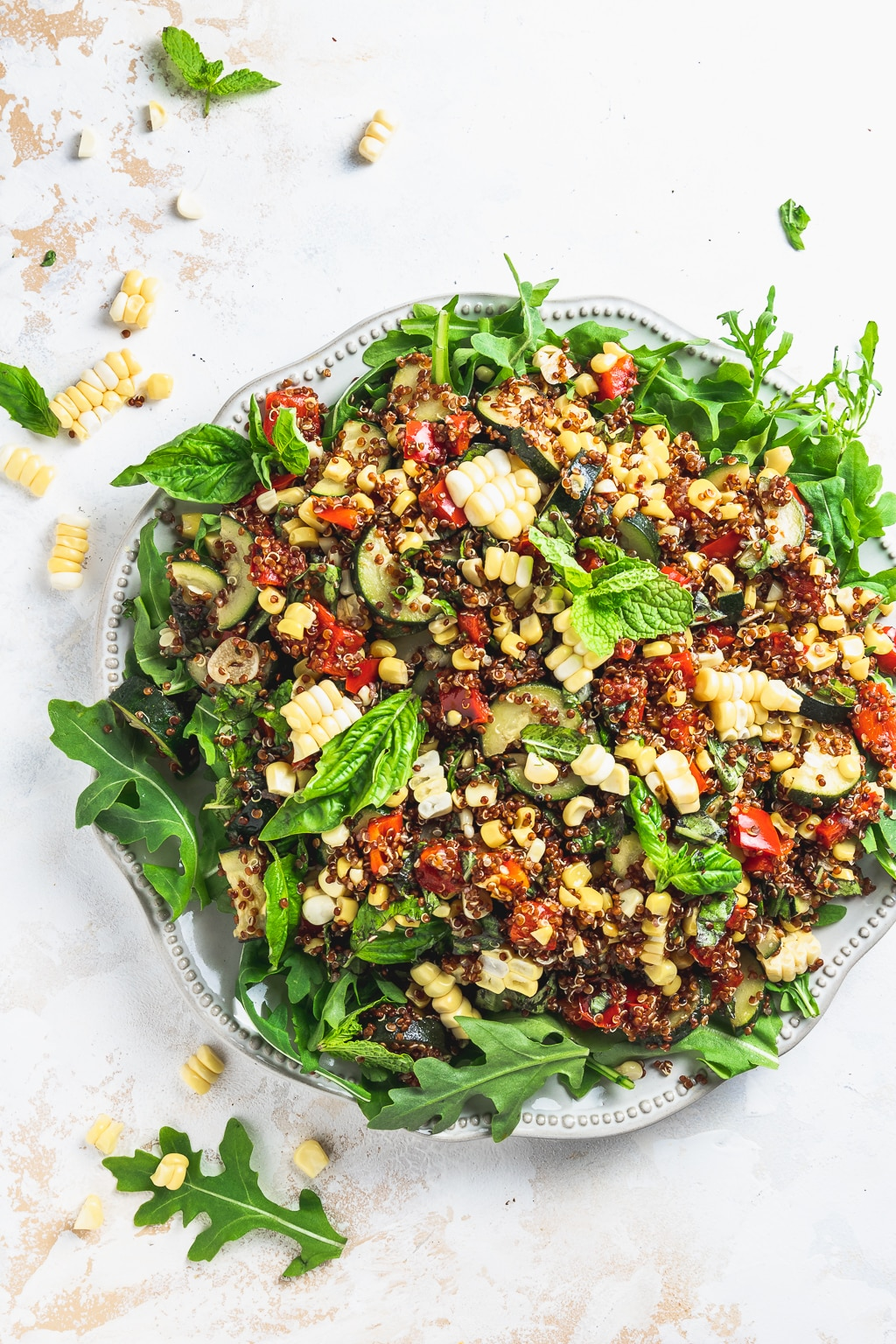zucchini corn quinoa salad on a plate with arugula and herbs