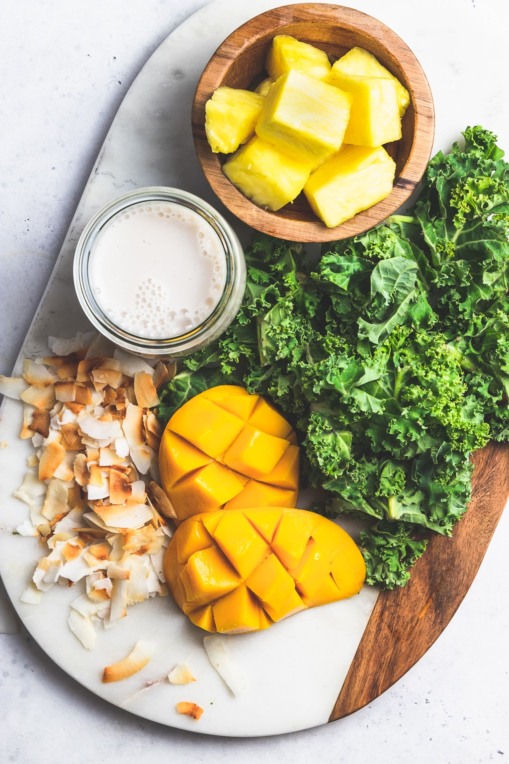 kale, mango, pineapple, almond milk, and coconut flakes on a wood and marble board
