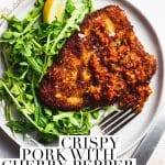 crispy pork cutlet with tomato cherry pepper relish and arugula, knife and fork.