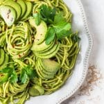 avocado tarragon pesto pasta on a plate with sliced avocados and lemon
