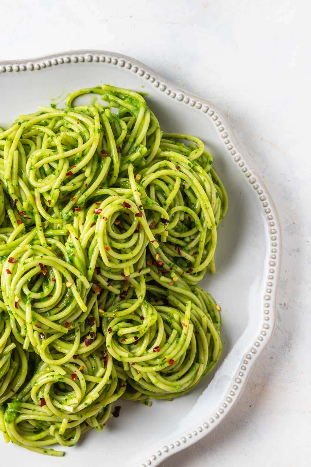 light grey plate of avocado tarragon pesto pasta