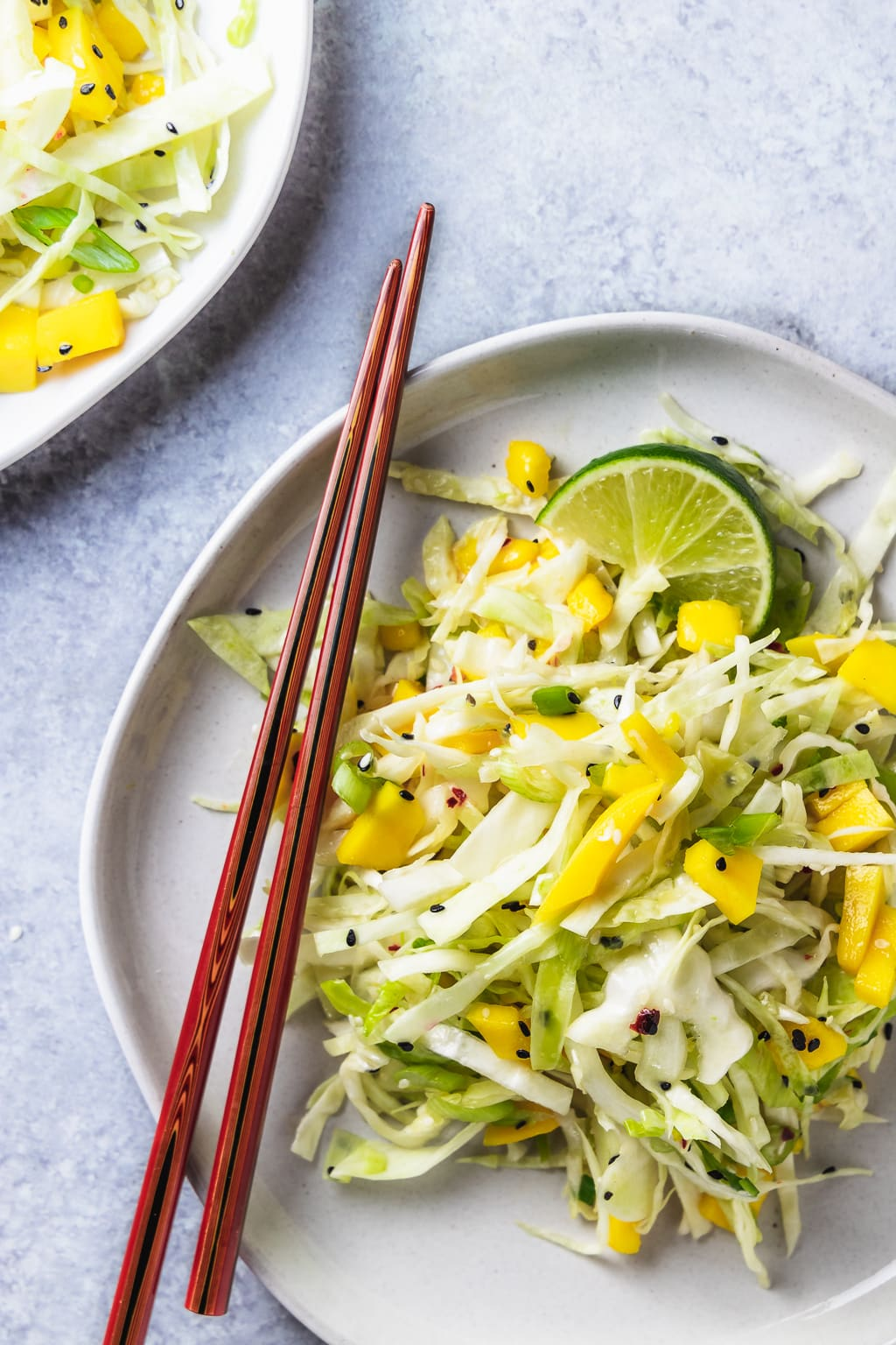 plate of mango sesame slaw on grey plate with chopsticks