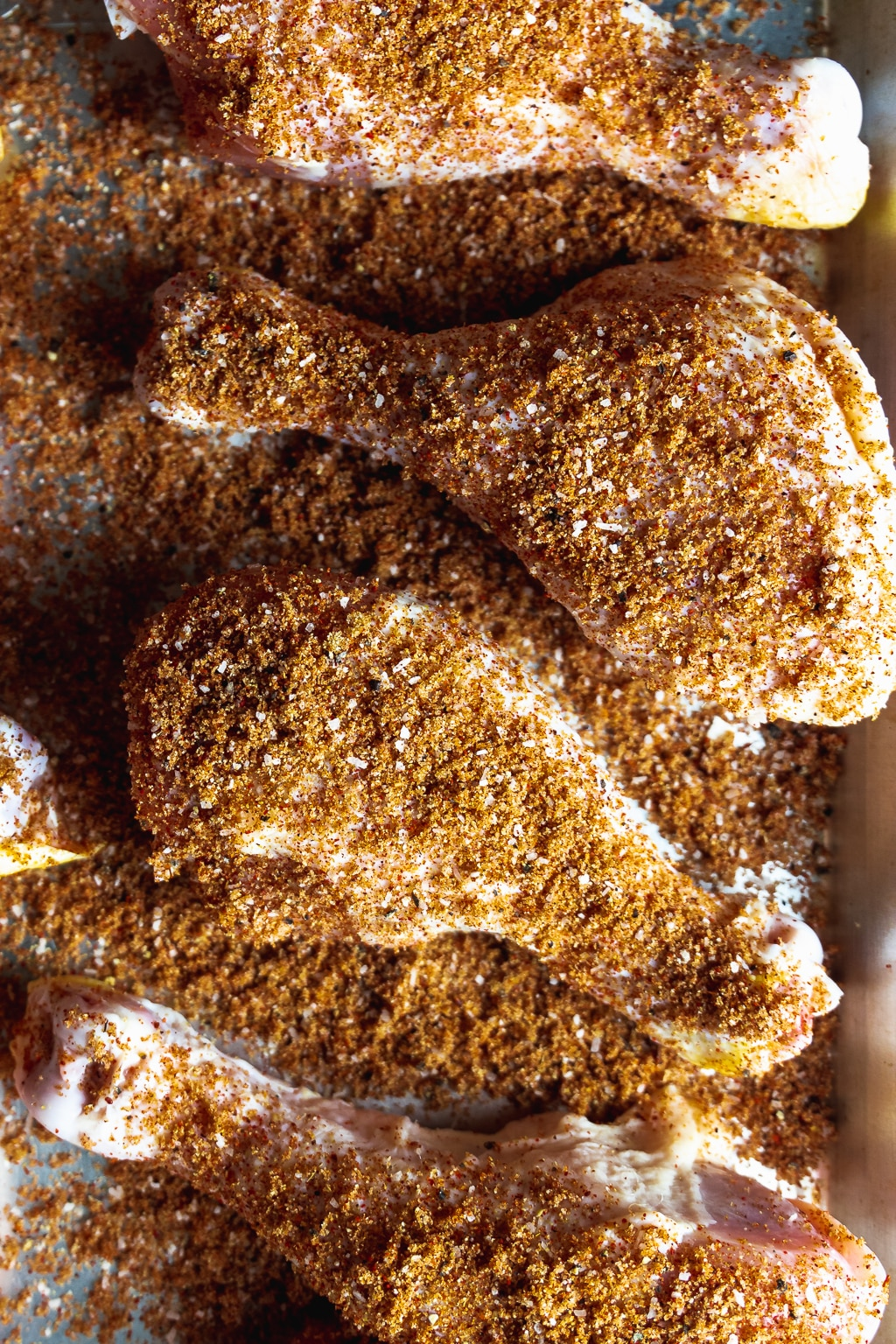 chicken legs sprinkled with barbecue rub seasoning